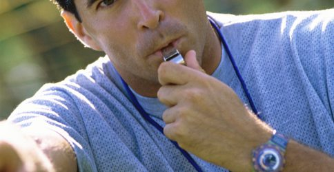Portrait of a coach blowing a whistle